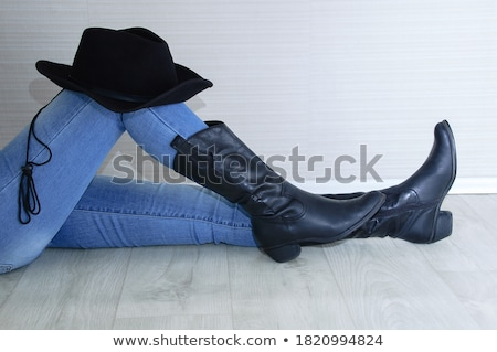 girl in jeans and a cowboy hat on wooden background stock photo © pzaxe