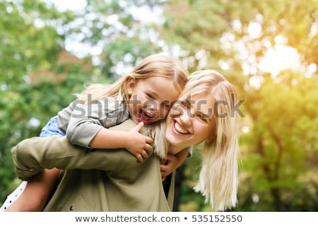 Child riding piggy back on her mother's back Stock photo © photography33