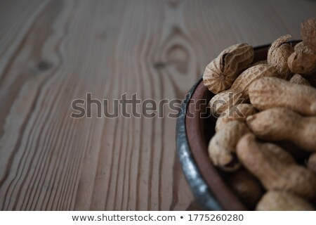 Macro shot of an opened peanut on a wooden table Stock photo © deymos
