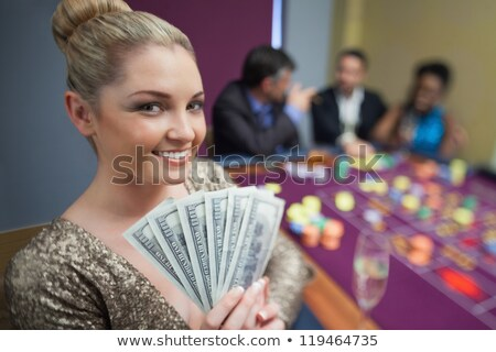 Blonde fanning dollars at roulette table in casino stock photo © wavebreak_media