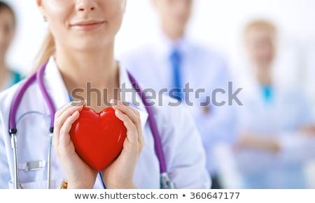 Női orvos sztetoszkóp tart piros emberi Stock fotó © HASLOO