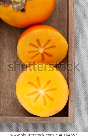 Two halves of persimmon in a wooden box stock photo © raphotos