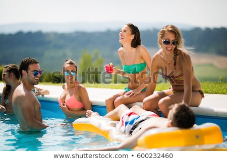 smiling young woman enjoying a drink in the pool stock photo © d13
