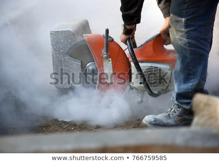 Construction Worker Cutting Stone With Circular Saw Stock photo © HighwayStarz