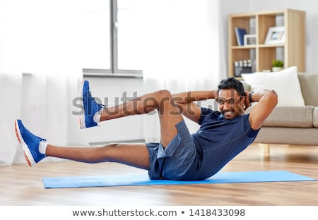 young asian man exercising abdominals on the floor at home stock photo © deandrobot