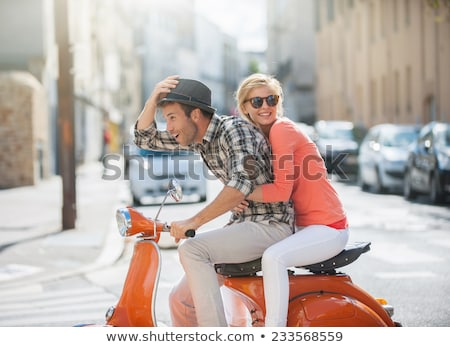 happy couple riding a scooter in old european town stock photo © deandrobot