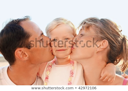 Stock photo: happy family with little near to sea parents kiss daughter