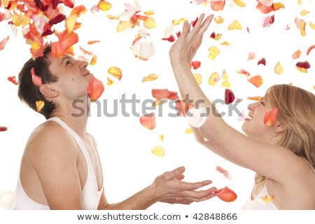 Attractive couple over falling rose petals Stock photo © konradbak