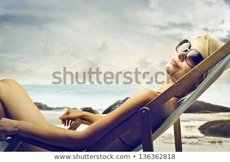 Beach sunglasses woman tanning relaxing in bikini stock photo © Maridav