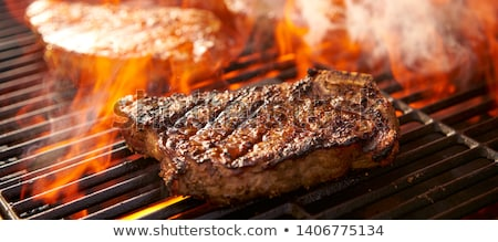 Flames grilling a steak on the BBQ Stock photo © zurijeta