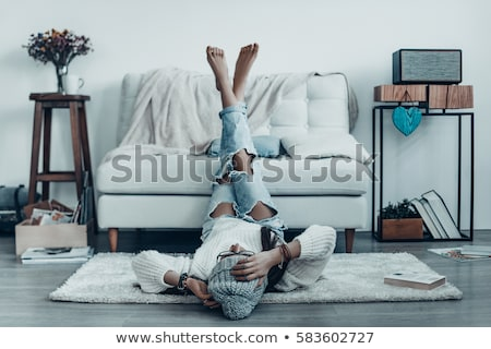 attractive woman in sweater lying on the carpet at home stock photo © deandrobot