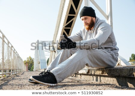 tired young man athlete in hat resting after workout stock photo © deandrobot