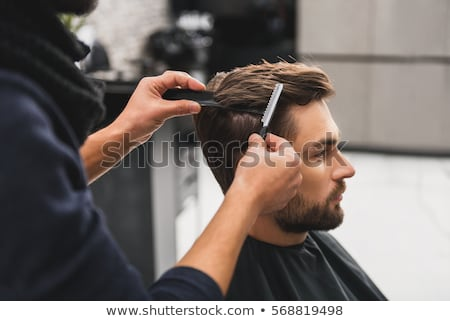 Man in barbershop getting haircut by hairdresser Stock photo © deandrobot
