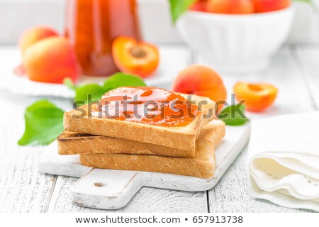 Stock photo: Toasts of bread with apricot jam and fresh fruit with leaves on white wooden table. Tasty breakfast.