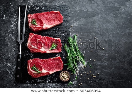 Raw meat, beef steak on black background, top view stock photo © yelenayemchuk