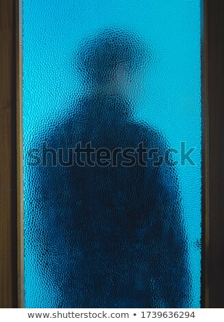 young man behind glass stock photo © is2