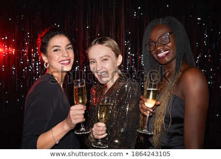 Young woman in nightclub holding up drink to camera and smiling stock photo © monkey_business