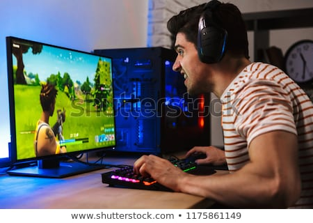 Portrait of caucasian gamer guy looking at screen while playing  stock photo © deandrobot