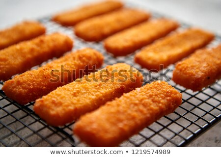 Rows of golden fried fresh fish fingers fillets Stock photo © dash