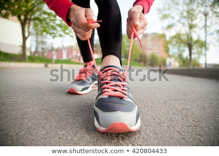 Sporty woman tying shoelace on running shoes before practice Stock photo © boggy