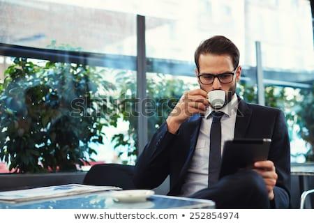 Businessman having breakfast and reading his tablet Stock photo © Minervastock