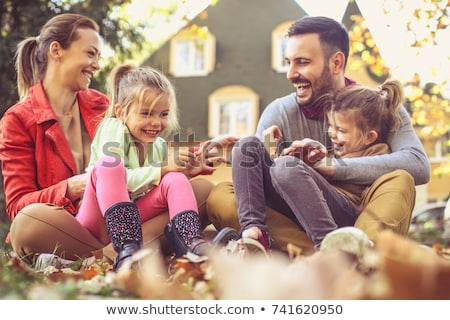 happy family playing with autumn leaves at park stock photo © dolgachov