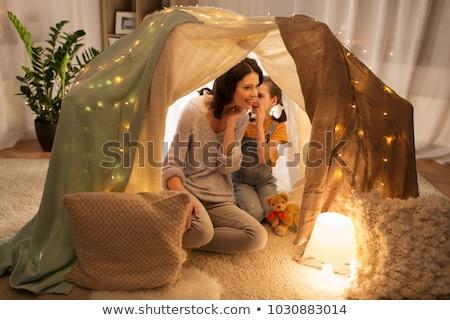 happy family whispering in kids tent at home stock photo © dolgachov