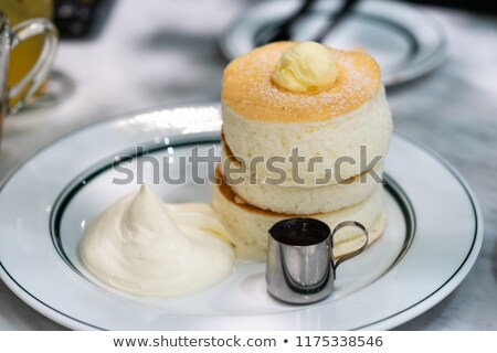A stack of scotch pancakes with with honey and blueberries on a breakfast table Stock photo © Melnyk