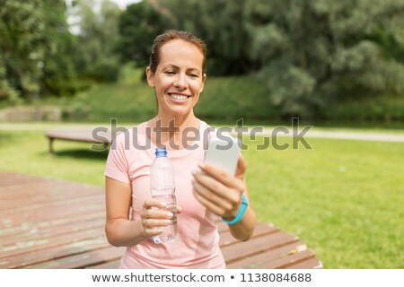 woman with smartphone drinking water in park Stock photo © dolgachov
