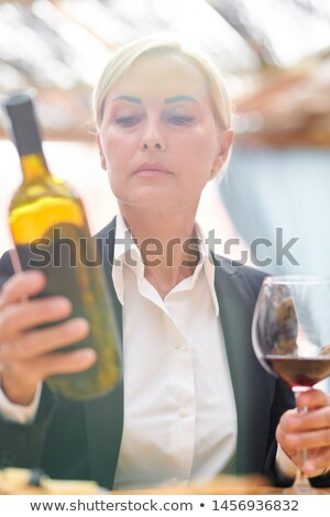 Mature blonde woman in formalwear looking at bottle of cabernet Stock photo © pressmaster