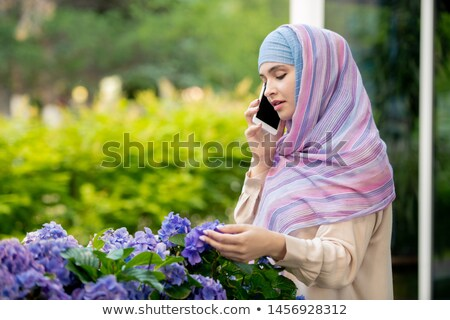 Young muslim woman in hijab talking on smartphone by flowerbed Stock photo © pressmaster
