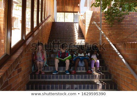 Front view schoolkids reading book between classmates while sitting on stairs of elementary school Stock photo © wavebreak_media