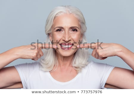 close up of woman pointing to her white teeth Stock photo © dolgachov