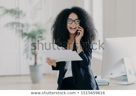 Pleased curly haired female director dressed in formal outfit, holds documents, calls via cell phone Stock photo © vkstudio