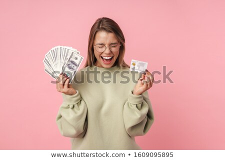 Portrait of nice excited woman holding banknotes and credit card Stock photo © deandrobot