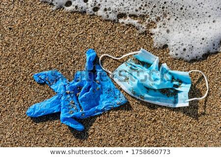 Usado máscara cirúrgica luvas areia azul Foto stock © nito