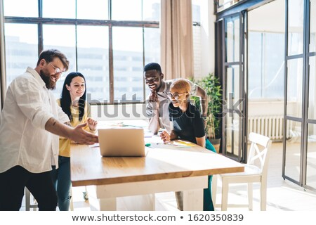 Colleagues gathered around laptop Stock photo © photography33