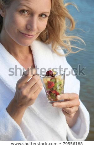 Smiling woman in toweling robe eating fruit salad Stock photo © photography33