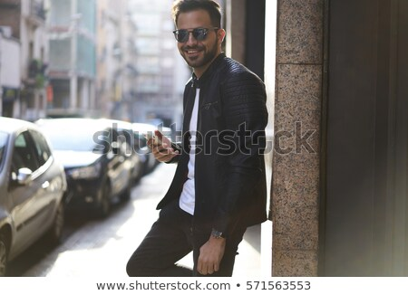 Handsome young man navigating on his smartphone Stock photo © stockyimages