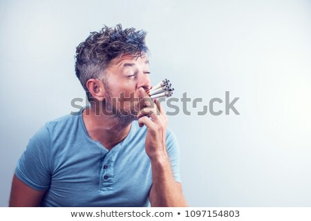 Angry smoker staring at cigarette Stock photo © stockyimages