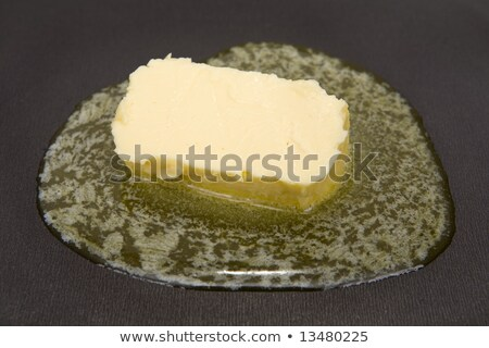 Piece of butter melting on non-stick frying pan Stock photo © ozaiachin