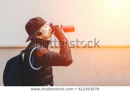 Fiatalember iszik energiaital szépség póló műanyag Stock fotó © ambro