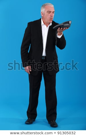 Man blowing dust off of a telephone Stock photo © photography33
