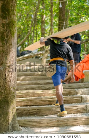 Stock photo: craftsman walking and holding a wooden board