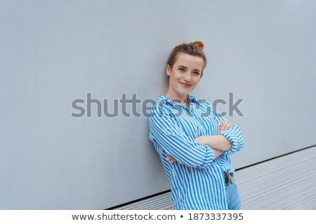 Smiling woman standing with arms folded against a white background Stock photo © wavebreak_media