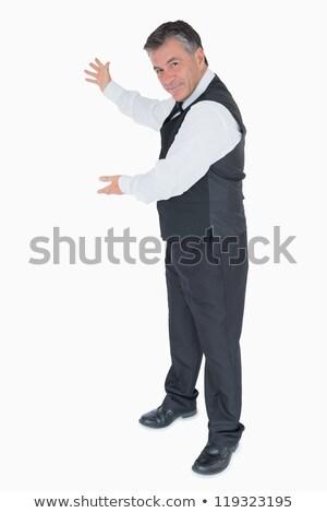 Waiter presenting something to the left on white background Stock photo © wavebreak_media