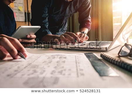 Designer drawing on graphic tablet with colleague Stock photo © HASLOO