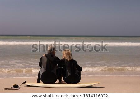 Rear view of senior man in wetsuit sitting by surfboard Stock photo © wavebreak_media