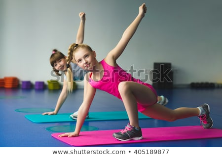 Stock photo: Young girl smiling and doing gymnastic exercises - stretching