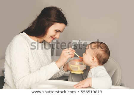 Young woman feeding daughter on table Stock photo © IS2